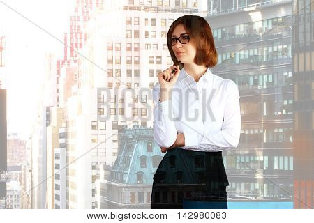 Thinking businesswoman on city background with copyspace. Double exposure