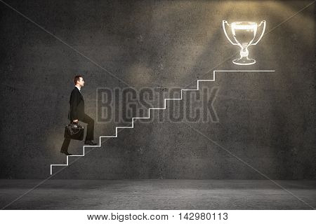 Success concept with businessman climbing abstract ladder sketch leading to winner's cup on concrete background