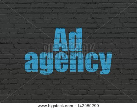 Advertising concept: Painted blue text Ad Agency on Black Brick wall background