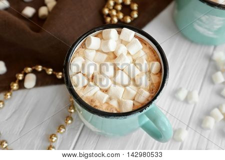 Mug of hot cocoa drink with marshmallows on table