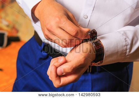 the groom dresses a watch. wedding day