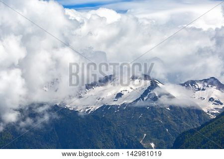 Big clouds over the snow-capped mountain peaks
