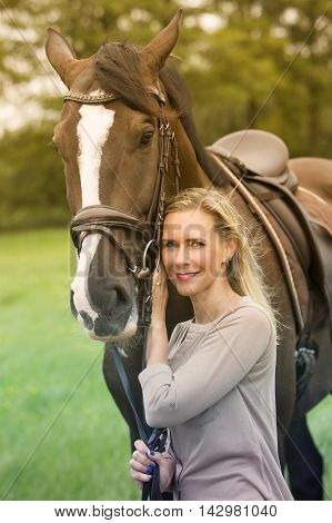 blond woman and her brown horse in nature