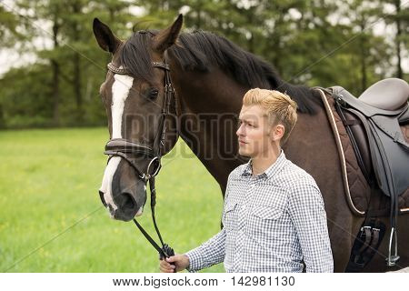 man walking with his brown horse on farmland