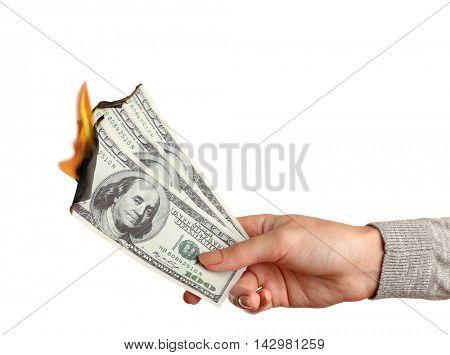 Female hand holding burning dollar banknotes on white background.