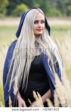 Long-haired blonde in a blue cloak in the field