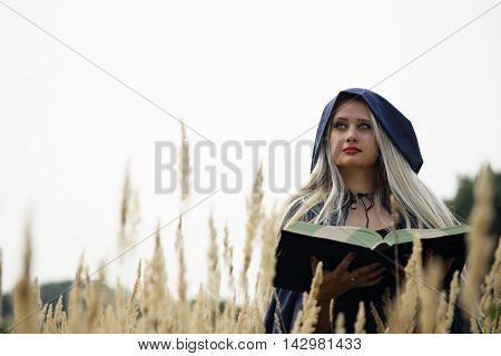 Long-haired blonde in a blue coat with a book