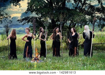 witches with brooms near a campfire in the meadow