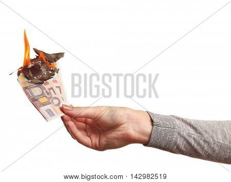 Female hand holding burning euro banknotes on white background.