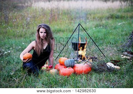 Witch preparing a potion in the meadow