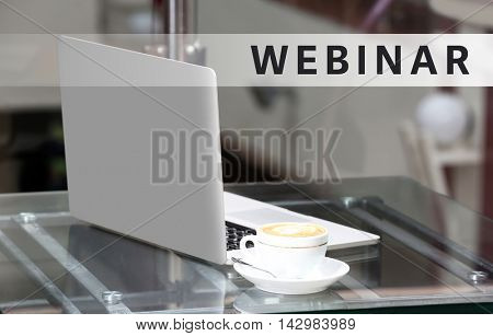 Business training concept. View on laptop and a cup of coffee on glass table, close-up