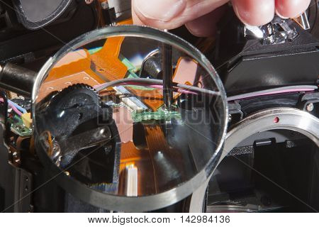 SLR camera repair with screwdriver and magnifier
