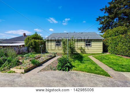 Backyard View Of Two Family House With Vegetable Beds.