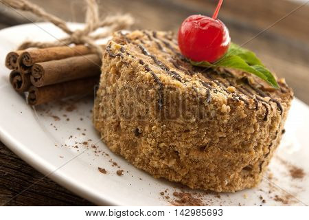 Layered Cake With Nut And Cinnamon On Plate, On Wooden Table, Dark Background. Selective Focus