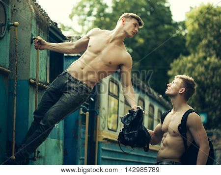 Handsome young guys with muscular body standing shirtless in pants with beautiful torso near blue old train railcar