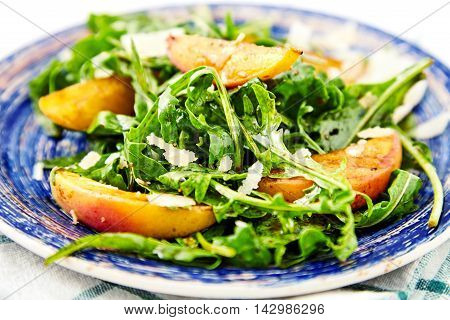 Arugula and peaches salad. Vegetarian gourmet salad made of caramelized grilled peaches slices, arugula leaves, parmesan cheese flakes and soy-vinaigrette dressing, close up. White wood background.