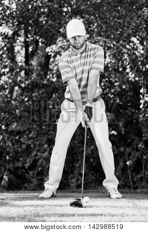 Young golfer ready to tee off, black and white image