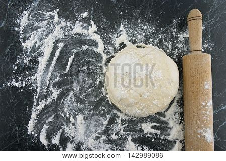 Freshly Prepared Dough On A Wooden Board. Rolling Pin And Flour On Table. Top View