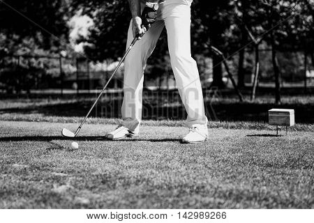 Golfer preparing tee-off with iron, black and white image
