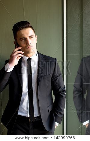 Man young handsome sensual elegant model in suit with skinny necktie open coat talks on mobile phone hand in pocket reflects in mirror on grey background