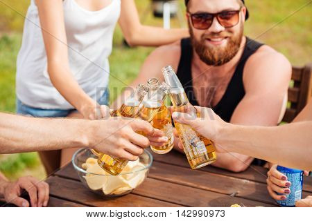Closeup of happy young friends drinking beer and cekebrating together