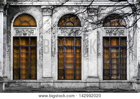 Facade of old abandoned building with three large arched windows of orange glass. Monochrome background