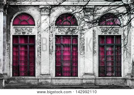 Facade of old abandoned building with three large arched windows of pink glass. Monochrome background