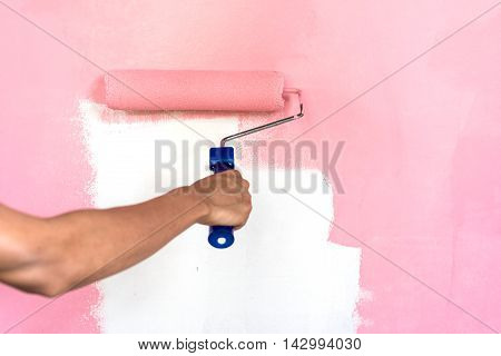 hand painting wall with paint roller brush