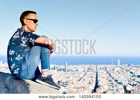 closeup of a young caucasian man at the top of a hill observing the city of Barcelona, Spain, below him
