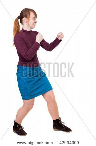 skinny woman funny fights waving his arms and legs. Isolated over white background. Girl with red hair tied in a ponytail in a boxing rack.