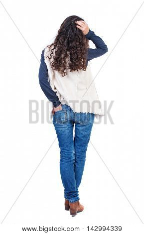 back view of standing young beautiful  woman.  girl  watching. Rear view people collection.  backside view of person. Long-haired girl with curly hair thoughtfully scratching his head.