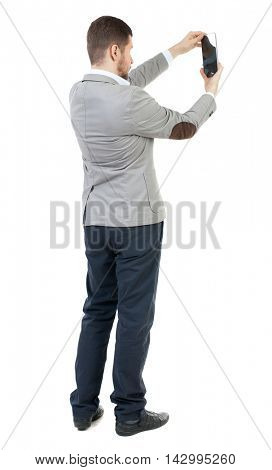 back view of standing business man photographing a phone or tablet. Rear view people collection.  backside view of person.  Isolated over white background. The bearded man in a gray jacket photographs