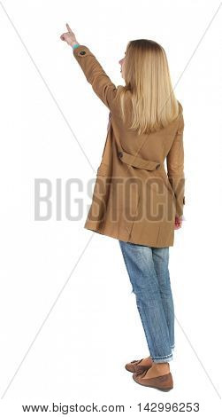 Back view of  pointing young women in parka. Young girl gesture. Rear view people collection.  backside view of person.  Isolated over white background. The blonde in a brown raincoat is pointing to
