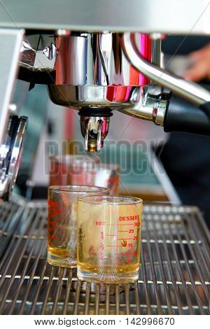 coffee machine brewing a coffee. Coffee pouring into shot glasses.