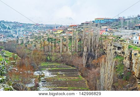 The kitchen gardens in Ihlara gorge with the colorful cottages on the rocky hill and Hasan volcano on the background Ihlara Cappadocia Turkey.