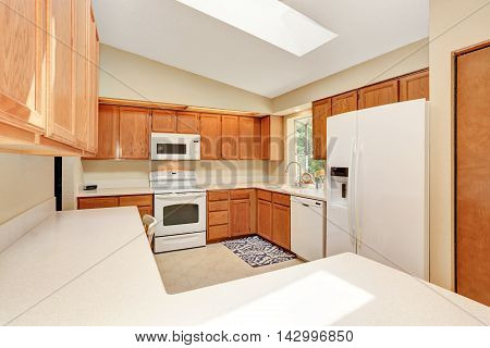 Kicthen In White Tones With Wooden Cabinets And White Counter Top.