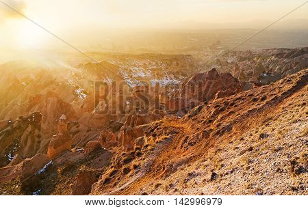 The amazing winter sunset over the Cappadocian Red Valley full of peaked cone colored rocks Turkey.