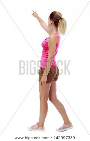 back view of pointing walking  woman. going girl pointing.  backside view of person.  Rear view people collection. Isolated over white background. Sport blond in brown shorts is by pointing to the sky