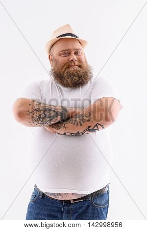 Fat bearded man is standing and posing. His arms are crossed with confidence. Isolated