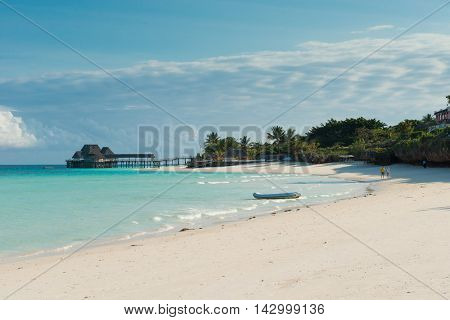beautiful view of wooden pier with thatched huts in ocean from sandy beach in Zanzibar