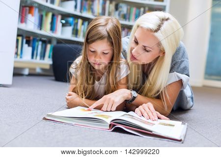 Mother With Daughter Read Book Together In Library