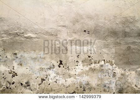 Cracked old plastered wall fragment background texture. Close up