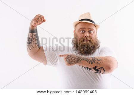 Look at my strength. Bearded fat man is pointing finger at his muscle. He is standing and looking at camera with confidence. Isolated