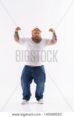 I am very strong. Fat man is standing and raising his arms. He is showing his muscles confidently. Isolated