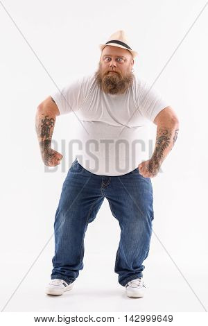 My strength is in my arms. Bearded thick guy is showing his biceps with seriousness. He is standing and posing. Isolated