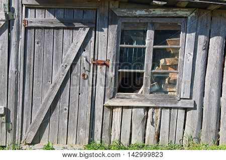 Old wooden barn with a closed door and broken window.