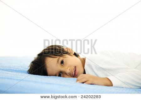 Garoto na cama, feliz hora de dormir no quarto branco