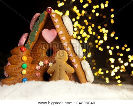 Funny gingerbread man in front of his candy house