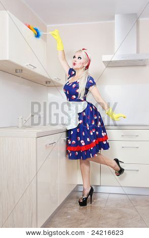 Beautiful housewife is cleaning the kitchen