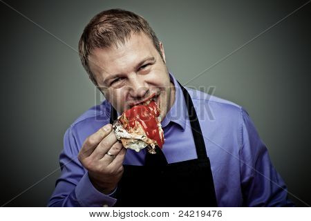 Hungry man eating chicken leg with anger